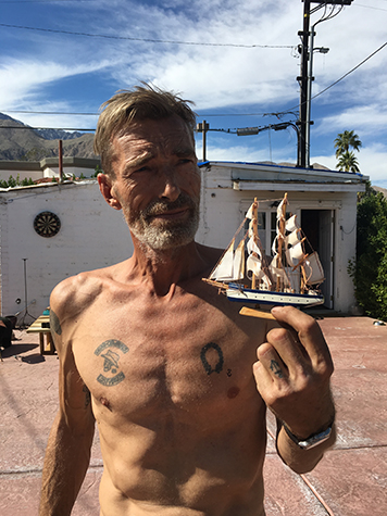 Artist Rudy De Rooy with a toy boat, outside Craig Krull Gallery's Small House Pop-Up Show in Palm Springs, 2016